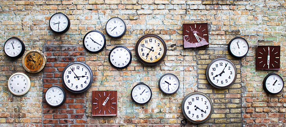 Collection of clock hanging on brick wall
